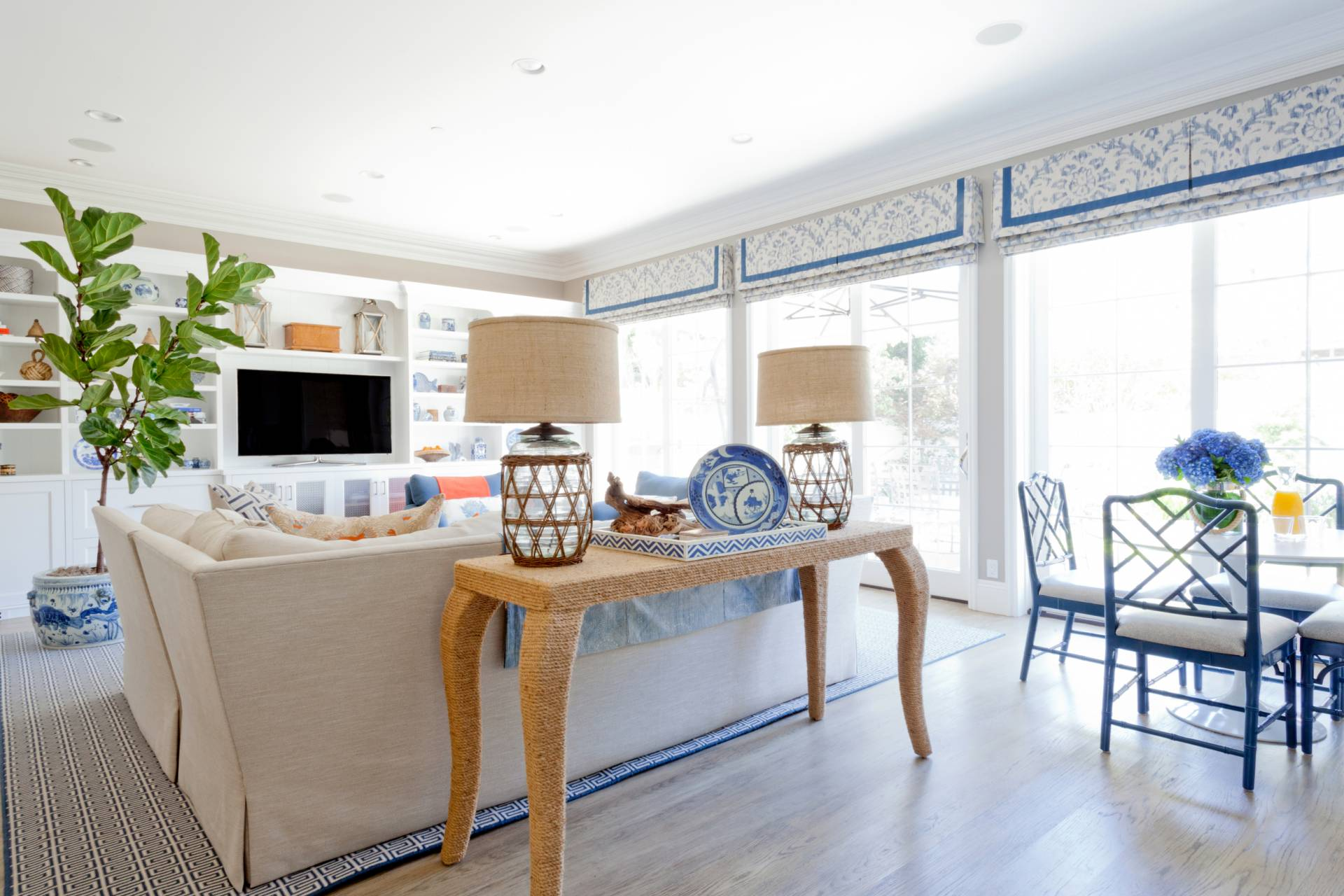 Blue and white roman shades with tan sofa