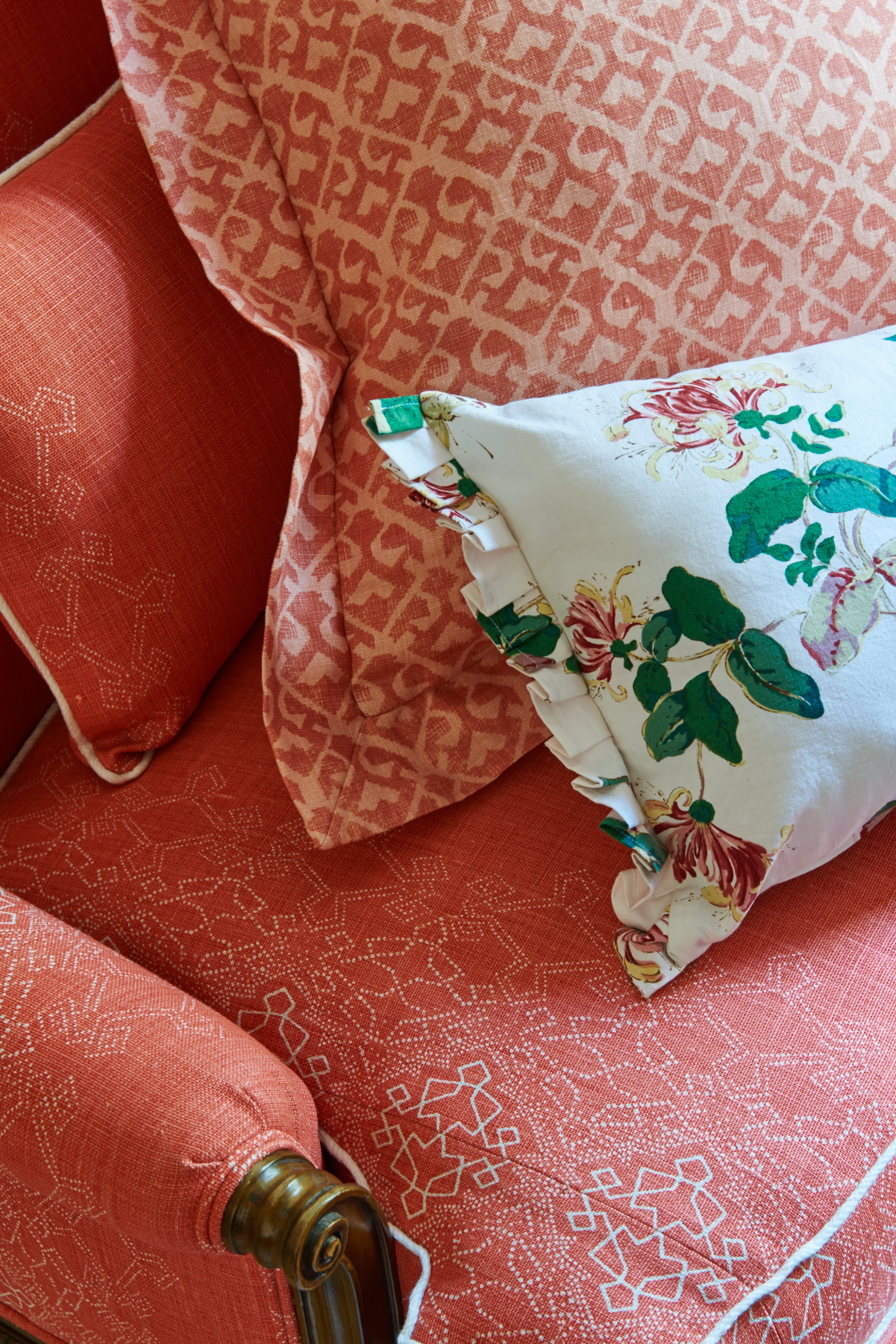 Red upholstered sitting chair with white piping and matching shams