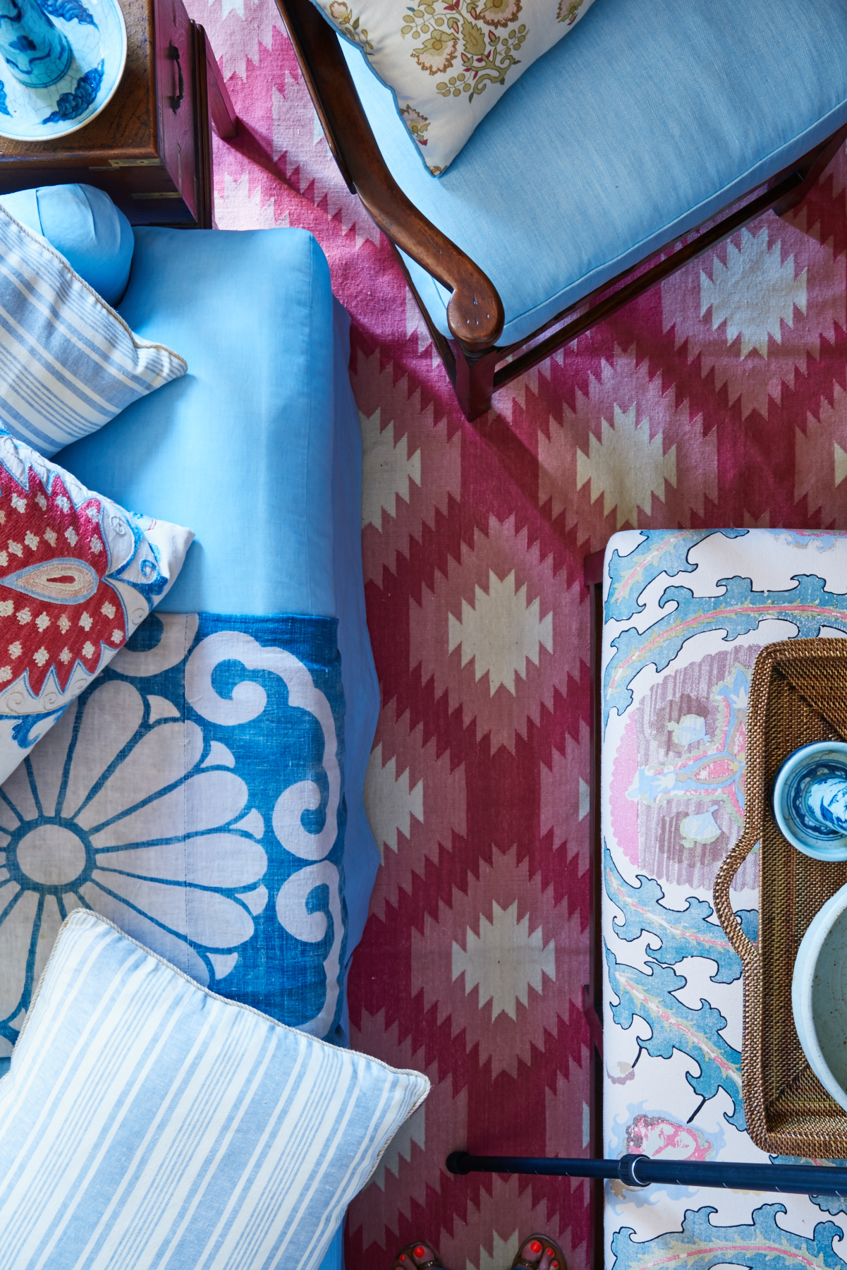 Various patterns of pillows and blue chairs