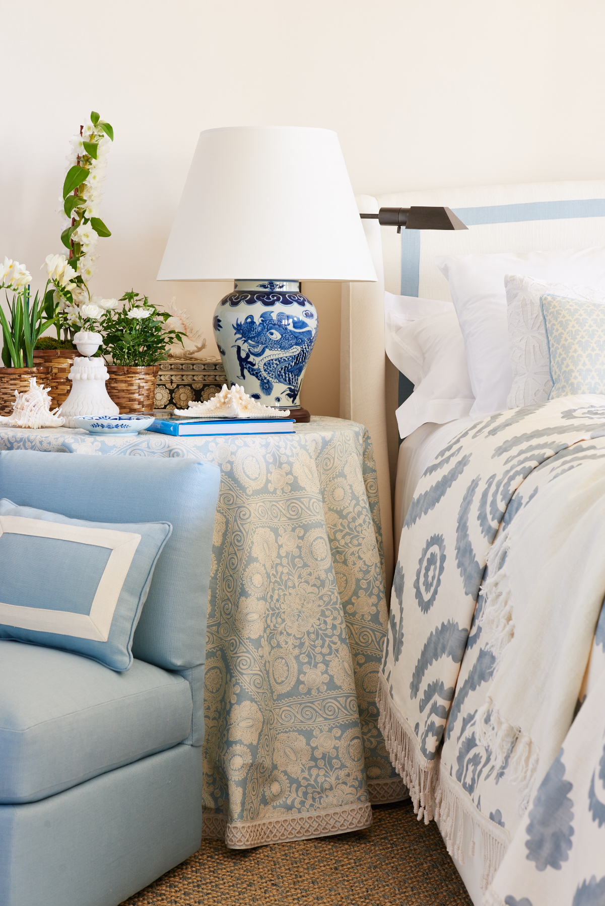 Light blue re-upholstered chair, table cloth, and bedding