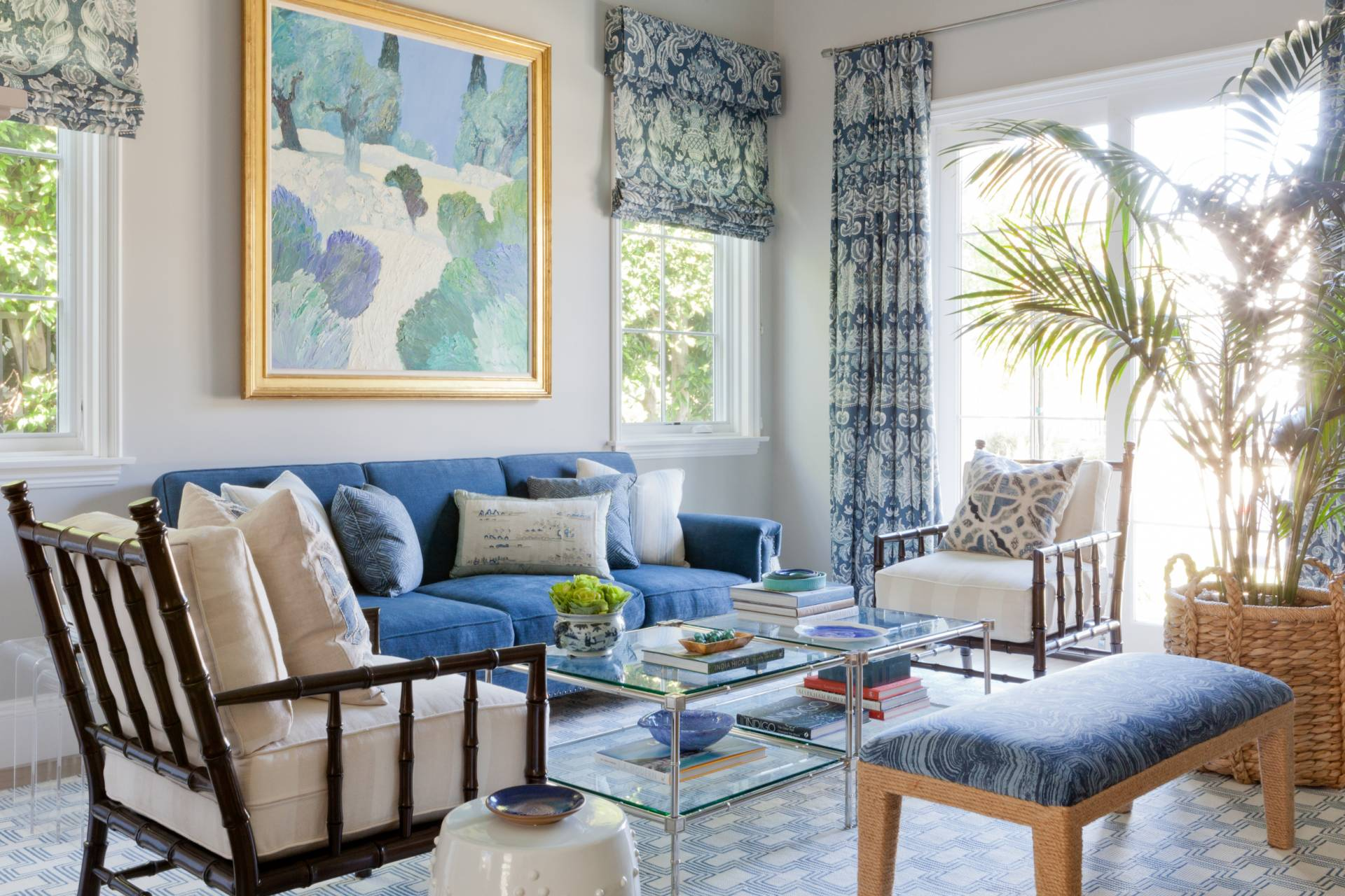 Blue and white roman shades, drapes on chrome rod, uphostered sofa and cushioned rattan chairs