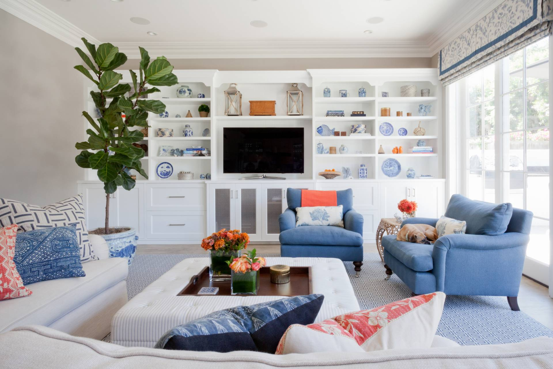 Blue stripe roman shades with white sitting chair, beige sofa and large custom ottoman