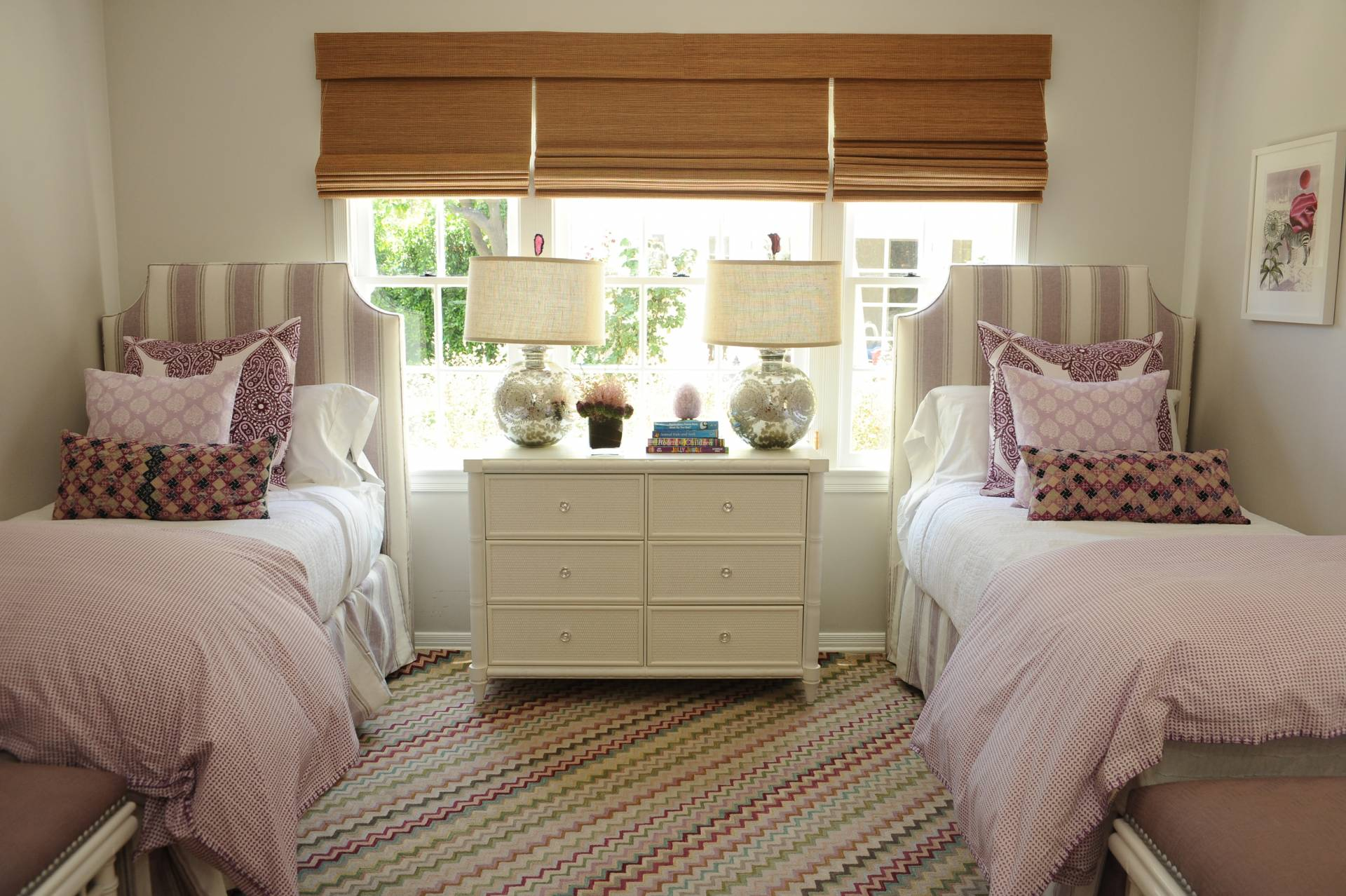 Woven shades in guest bedroom with upholstered headboard and bedding