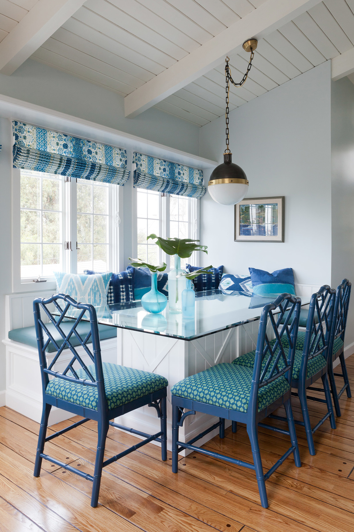 Blue and white roman shades and upholstered dining chairs