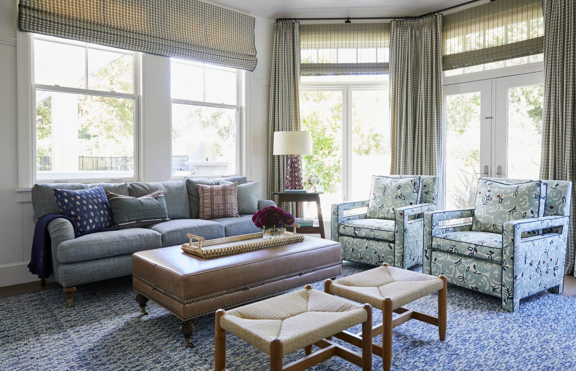 Wide view of living room with herringbone sofa, paisley sitting chairs, checkered drapes, and woven wood shades