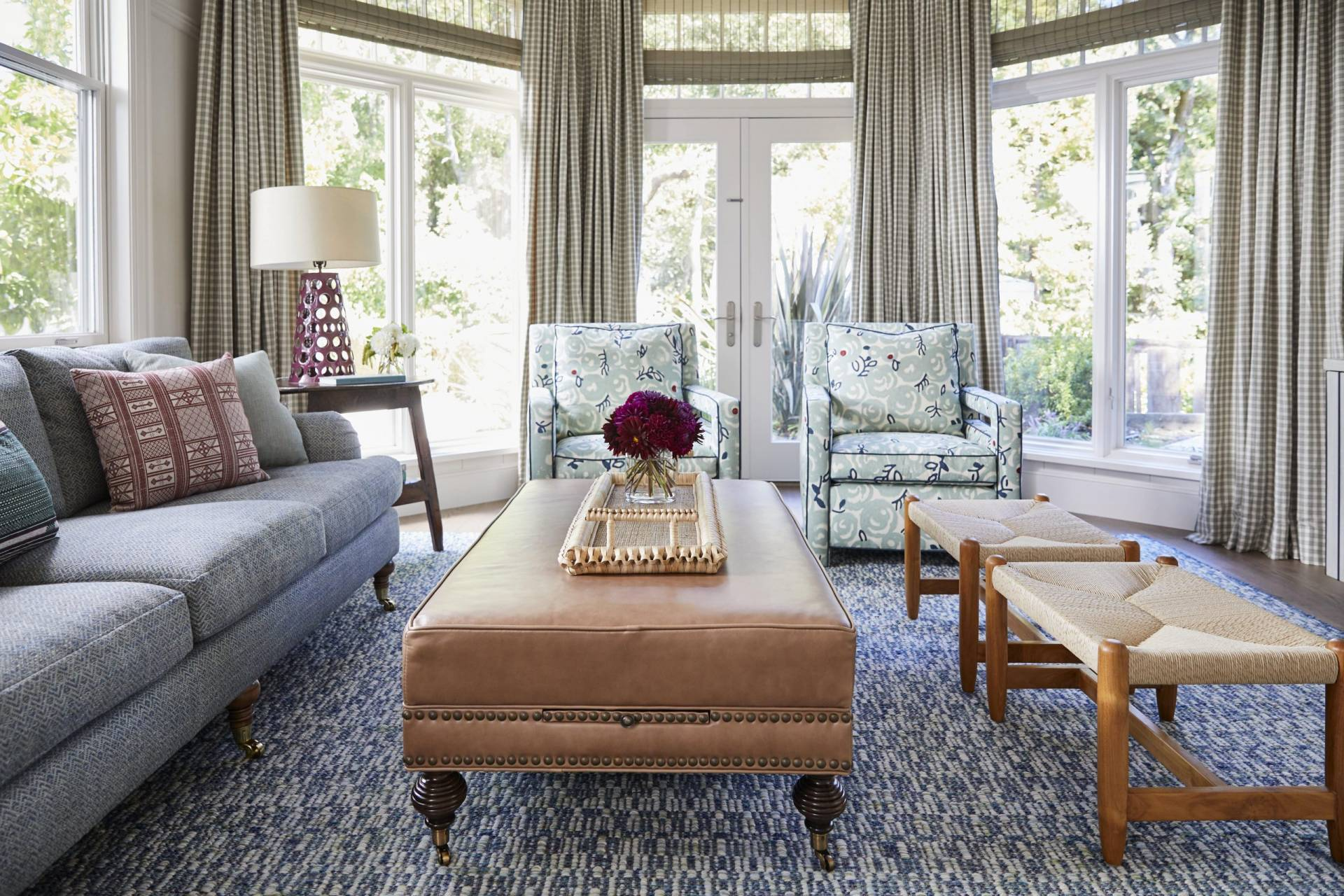 Living room with herringbone sofa, paisley sitting chairs, checkered drapes, and woven wood shades