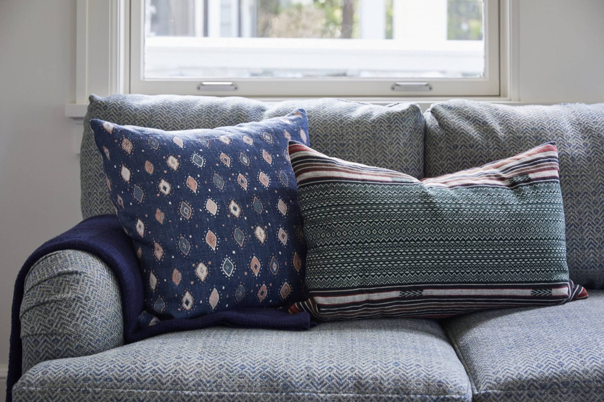 Blue herringbone sofa with patterned throw pillows