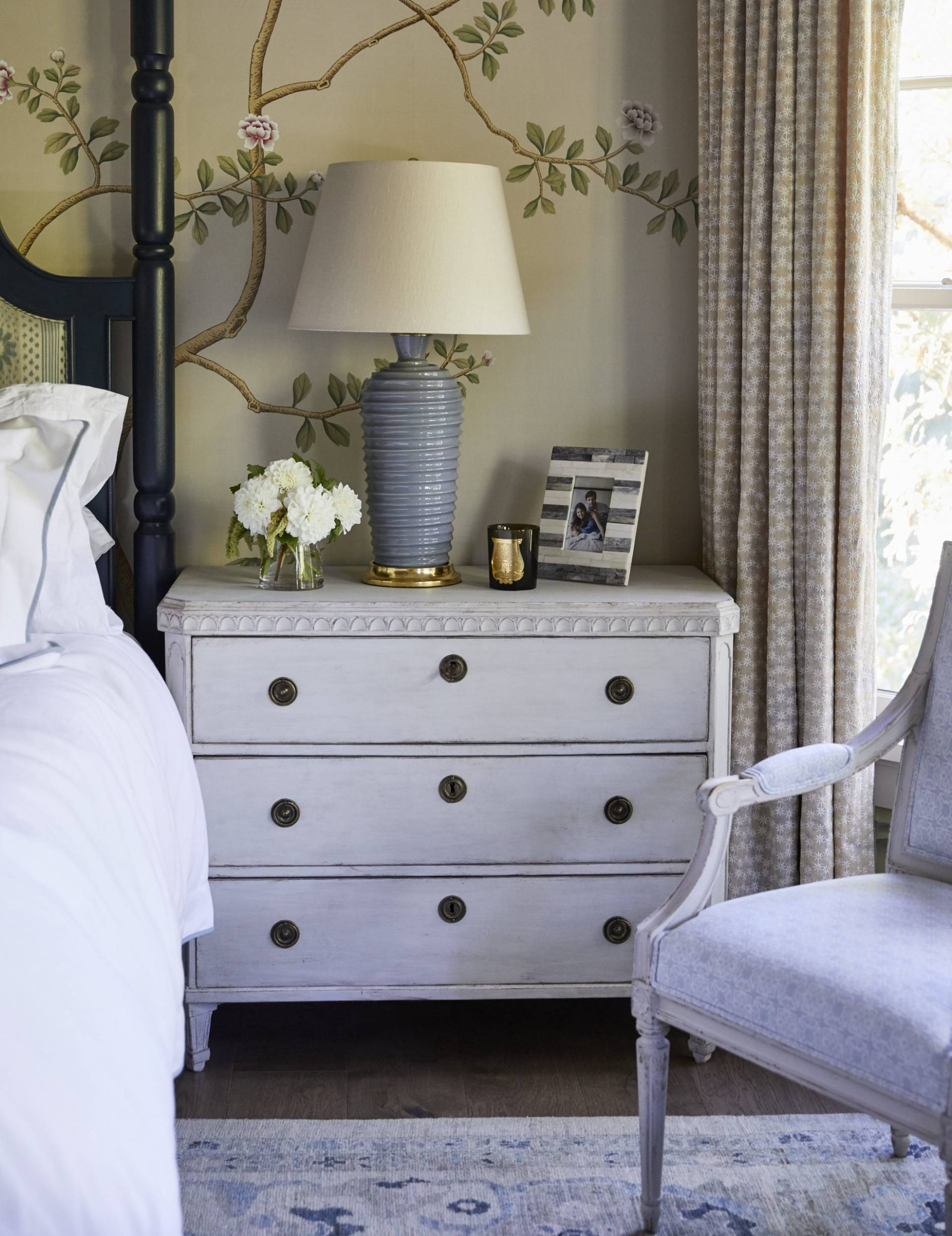 Bedroom armchair and patterned drapery against wallpaper