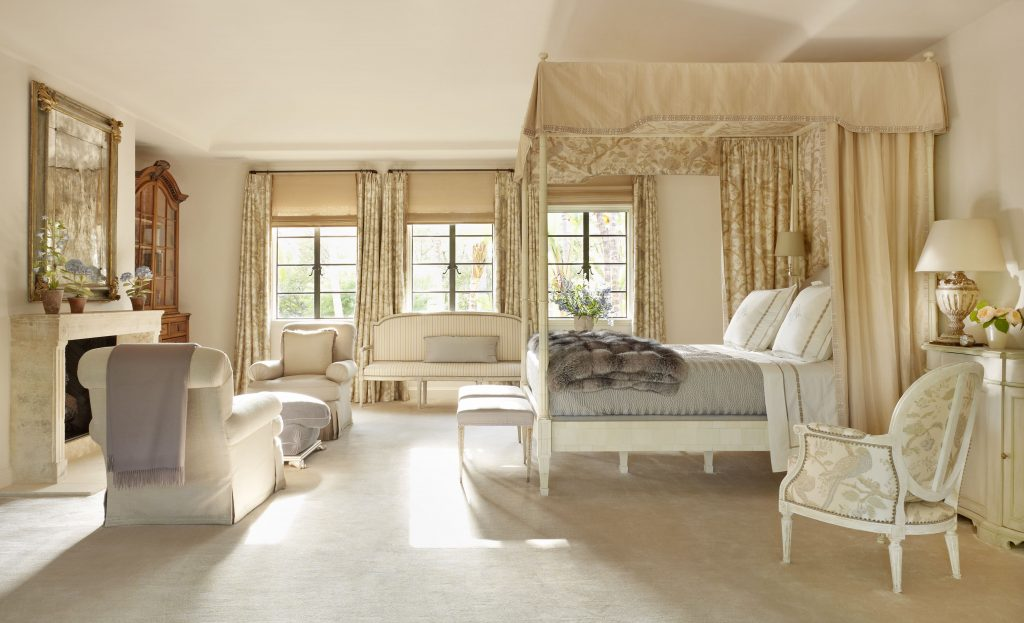 Shades of gold bedroom with bed canopy, pleated drapery, roman shades, and upholstery