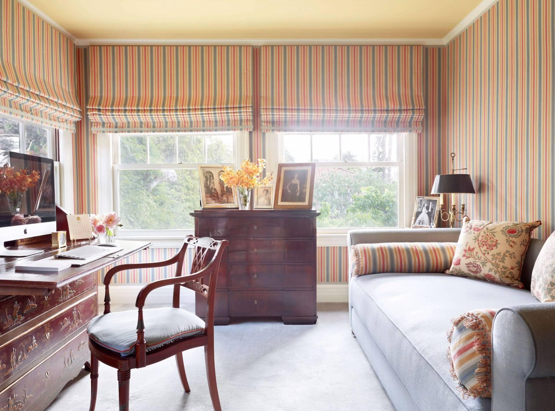 Vertical orange striped roman shades in office