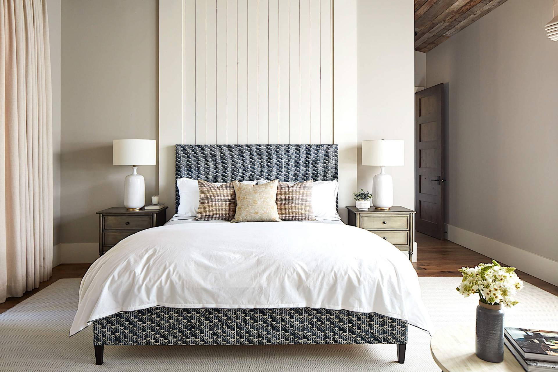 Contemporary master bedroom with pillow shams and upholstered bed