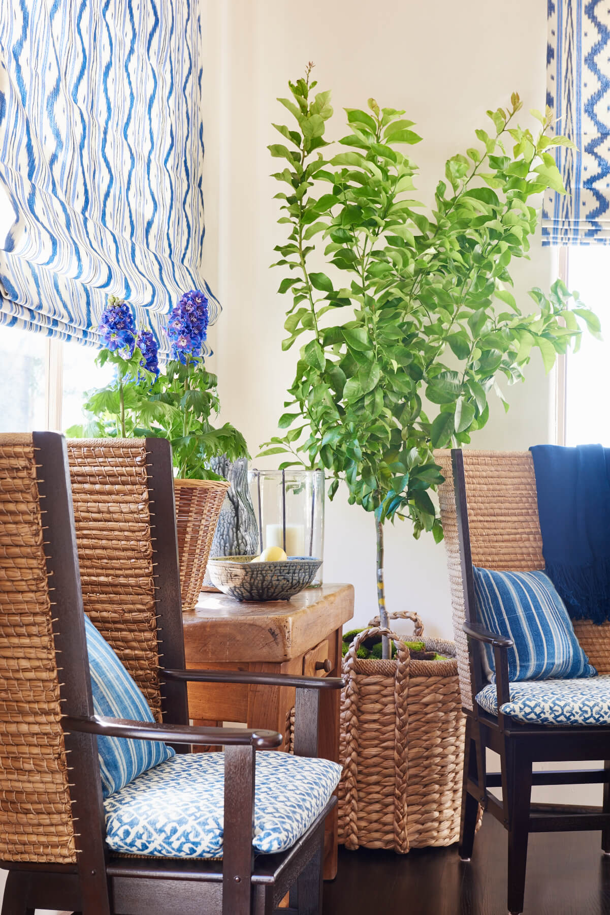 Blue upholstered rattan dining chairs with matching roman shades