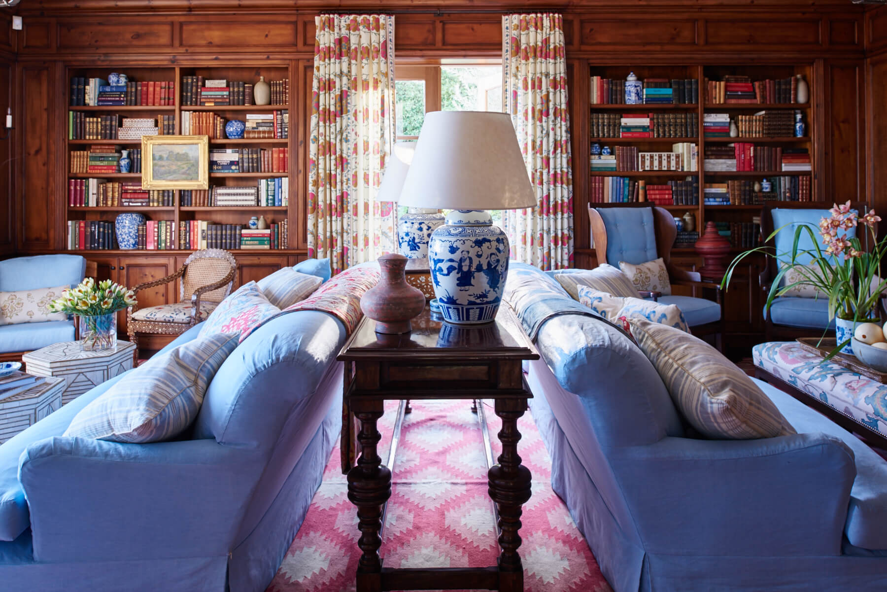 Blue upholstered sofa and chairs with red patterned drapery in the library