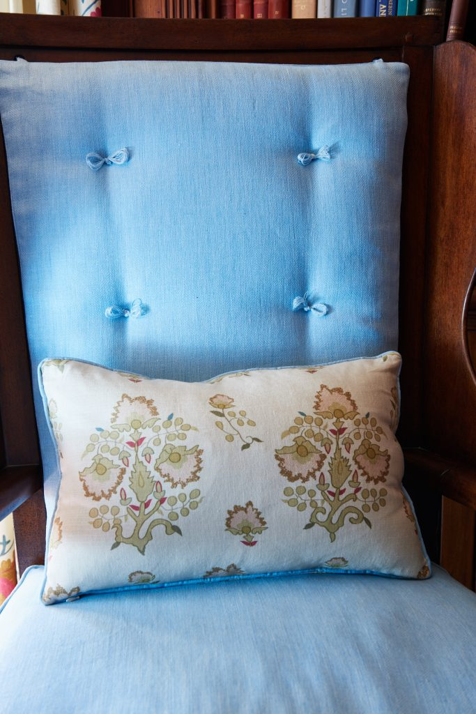 Blue upholstered chair with bow tie button accent