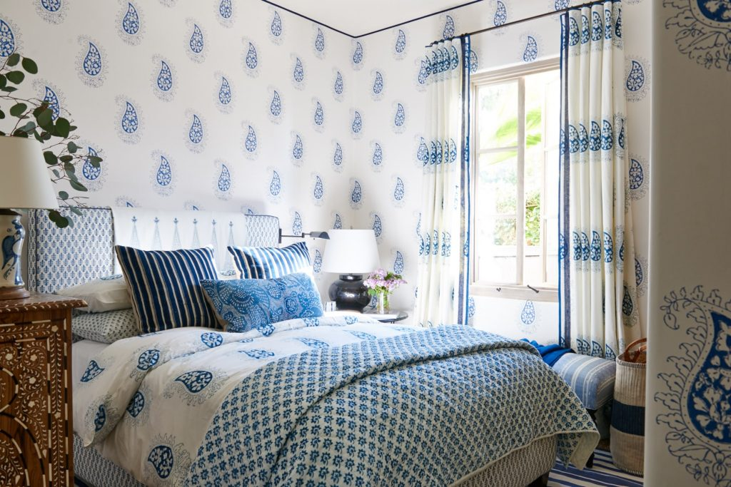 Teardrop pattern blue and white drapery with contrast lead edge, bedding, upholstered headboard, and wallpaper