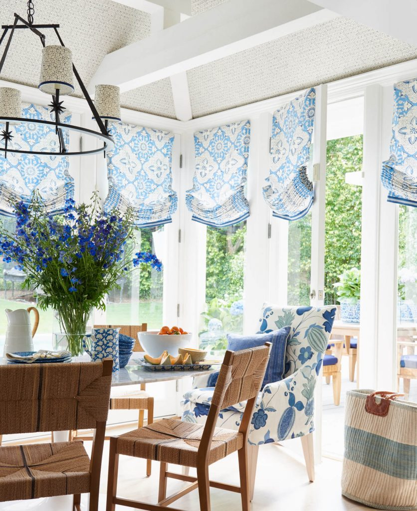 Sunroom blue roman shades and upholstered dining chairs