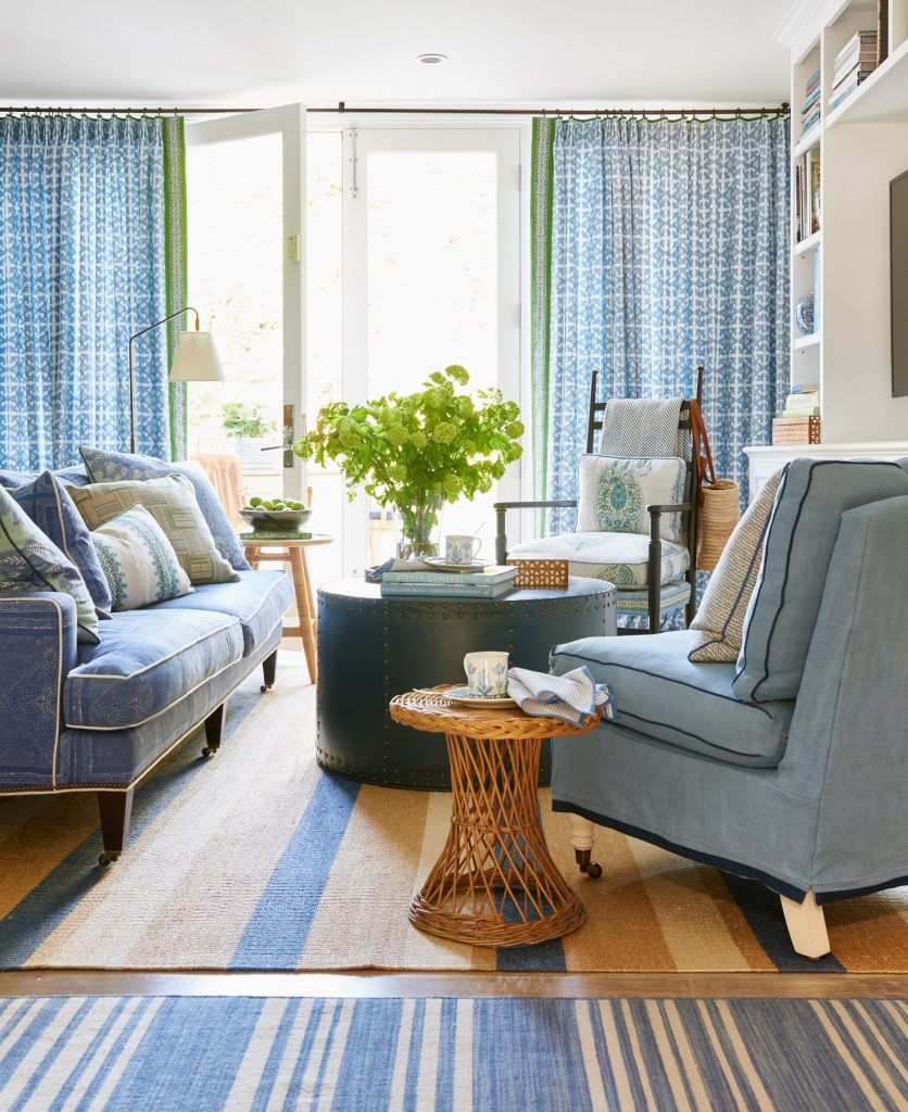 Sheer blue drapes on long iron rod with contrast edge and upholstered seating with contrast trim