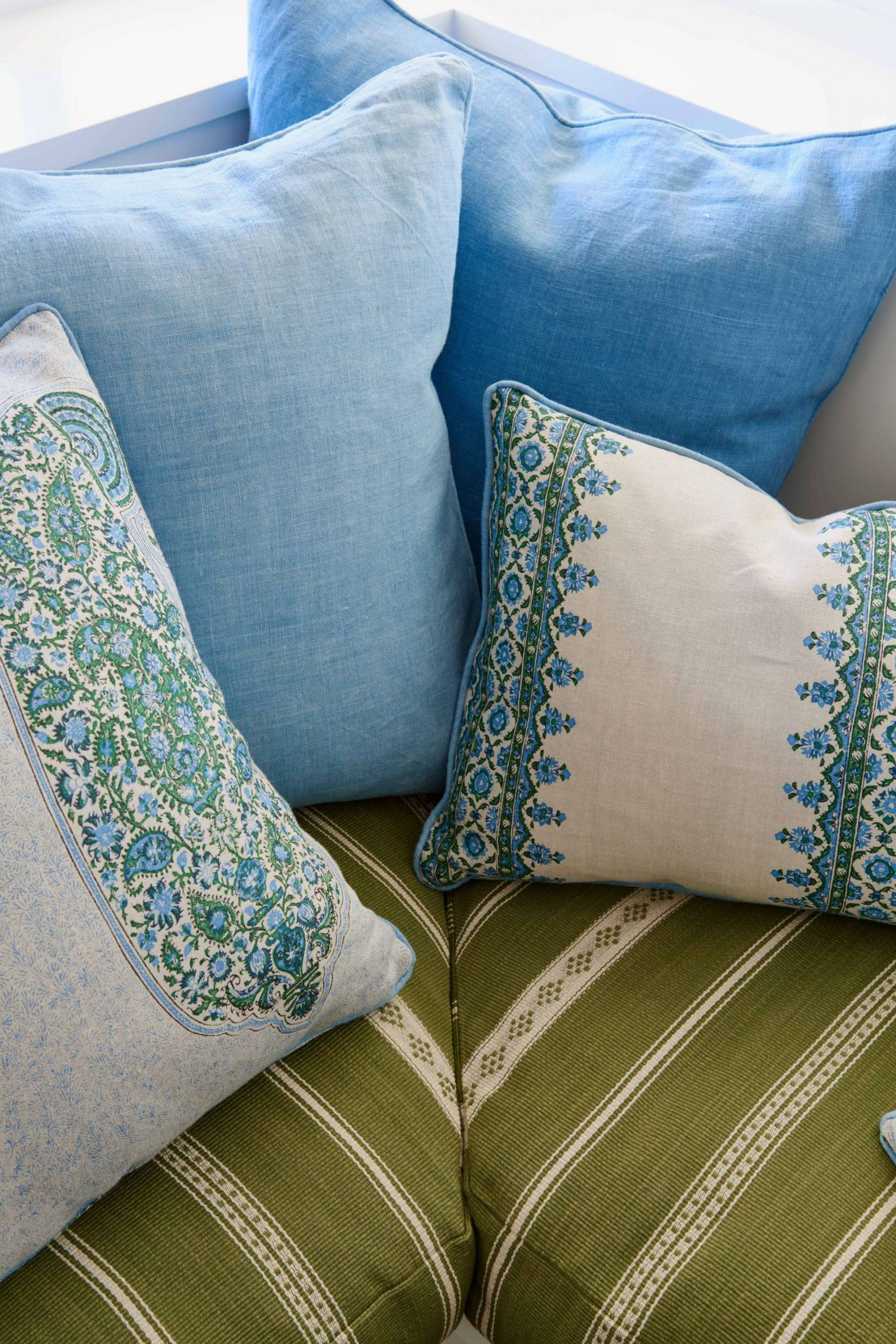 Patterned Blue and Cream Throw Pillows on Upholstered Bench