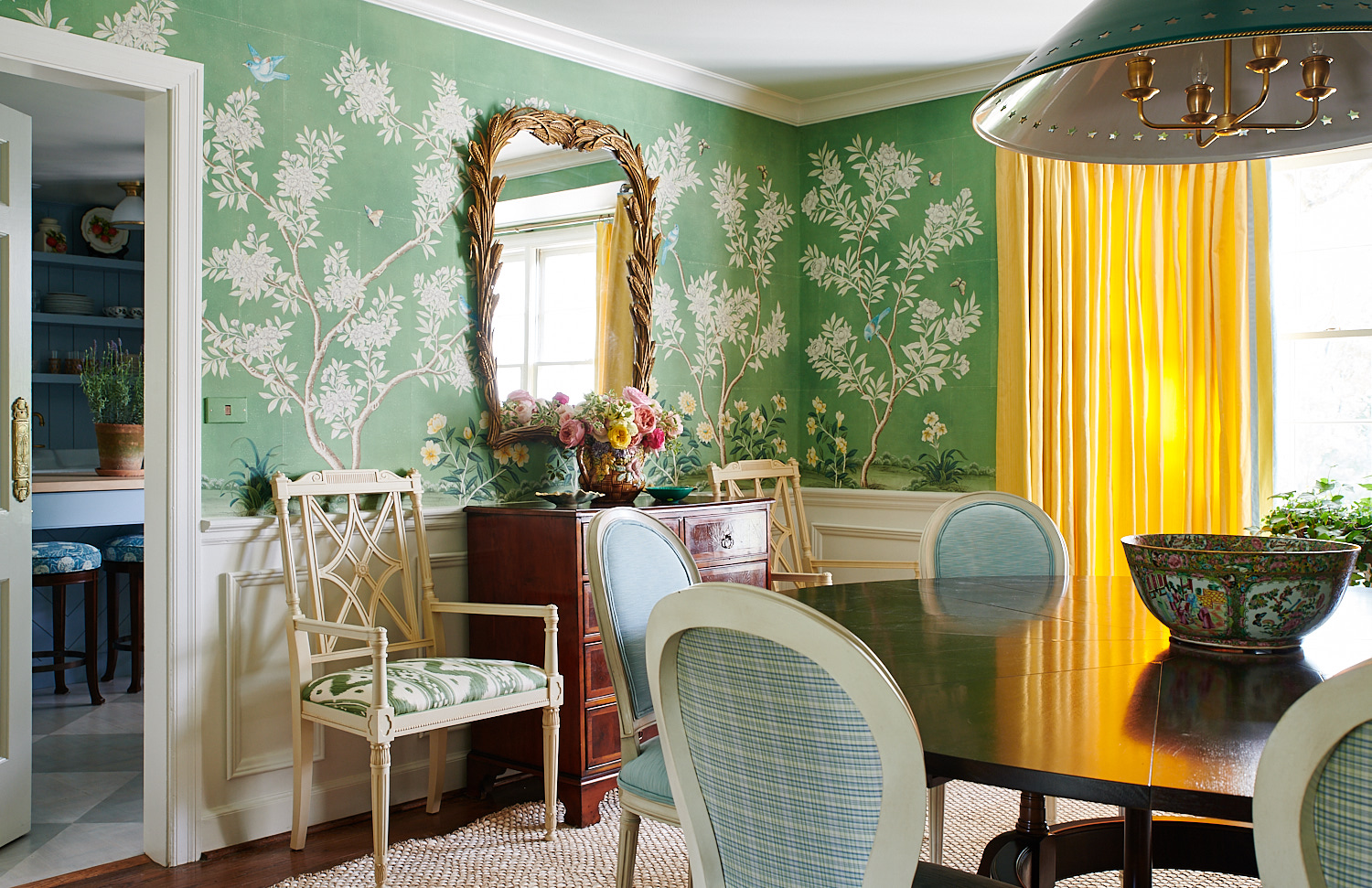 Mustard drapery, upholstered wall chairs, and dual plaid and textured upholstered dining room