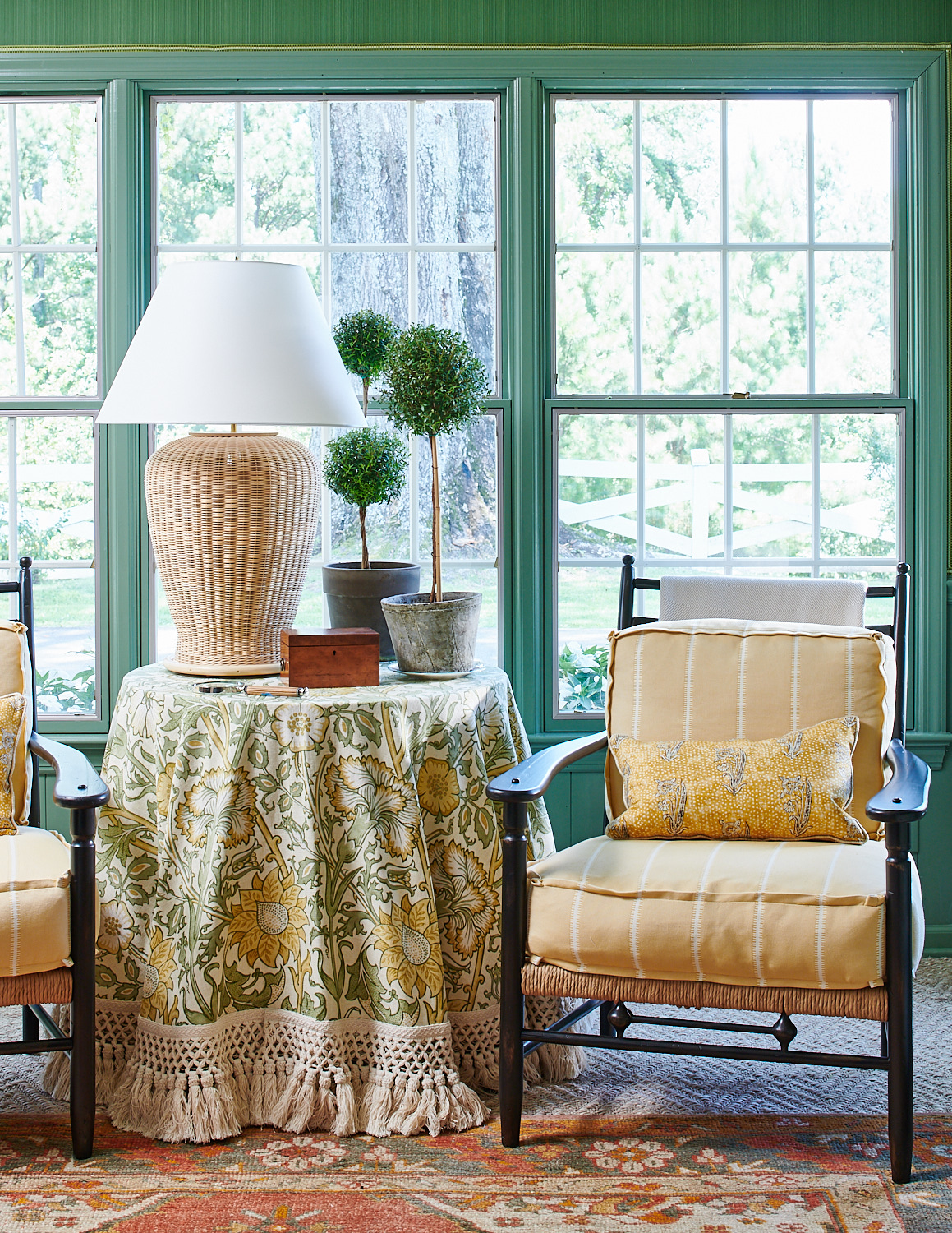 Cane wicker chairs with vertical-striped cushions and kidney pillows