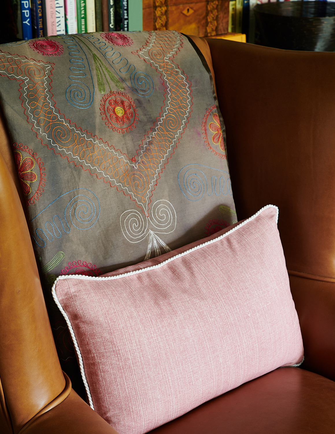 Detail of burnt-orange leather chair with custom pink kidney pillow and trim