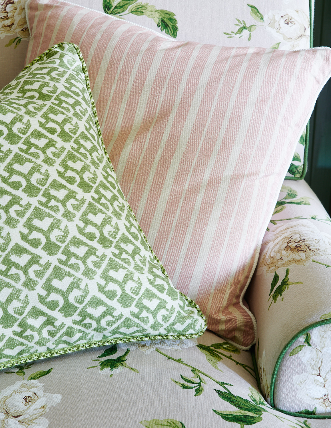 Customs pillows with trims on upholstered floral chair