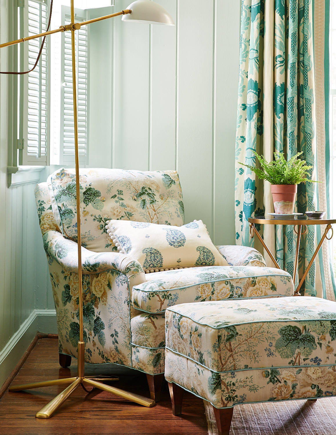 Upholstered floral chair with kidney pillow and tassels, and matching ottoman