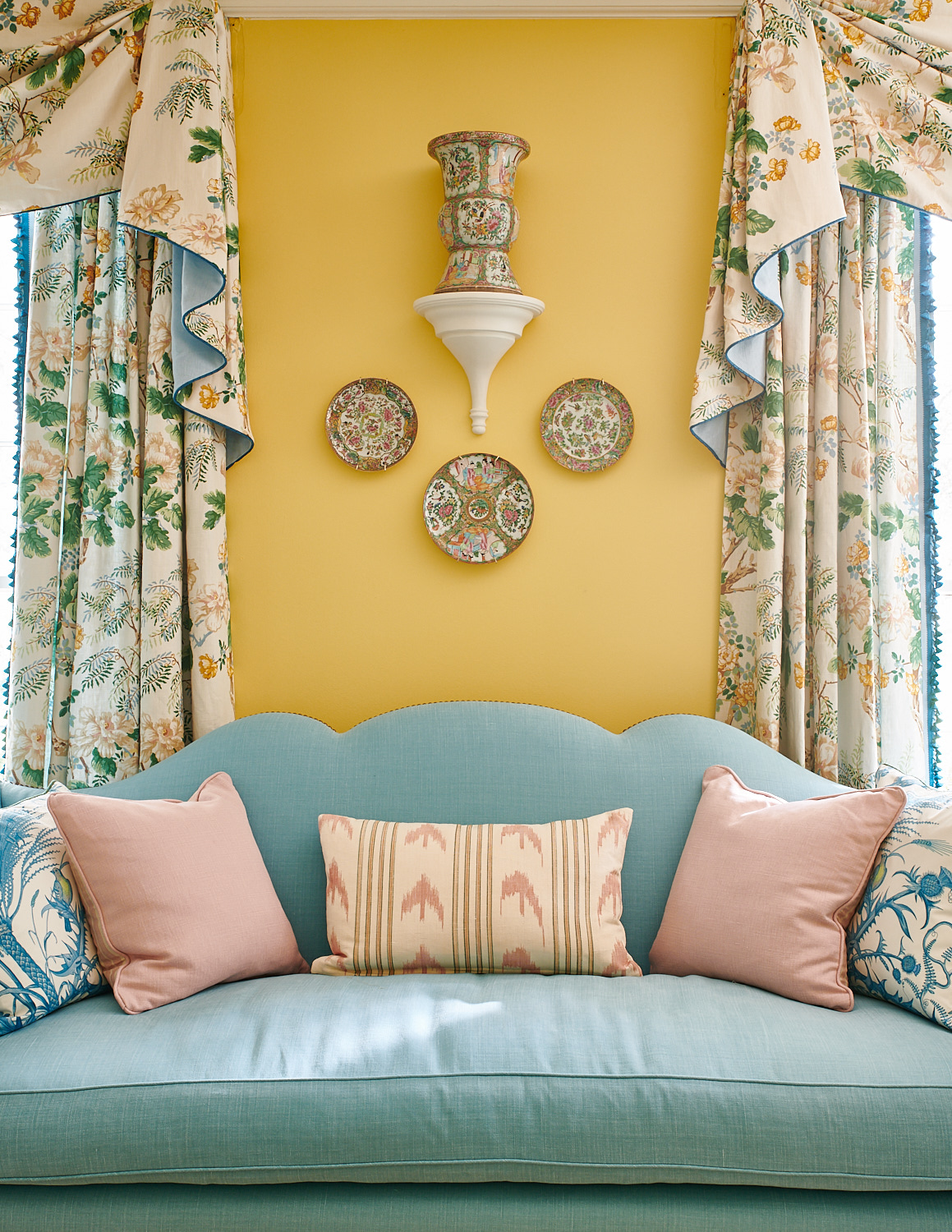 Upholstered baby blue sofa with custom pillows, and drapery with matching pick-up