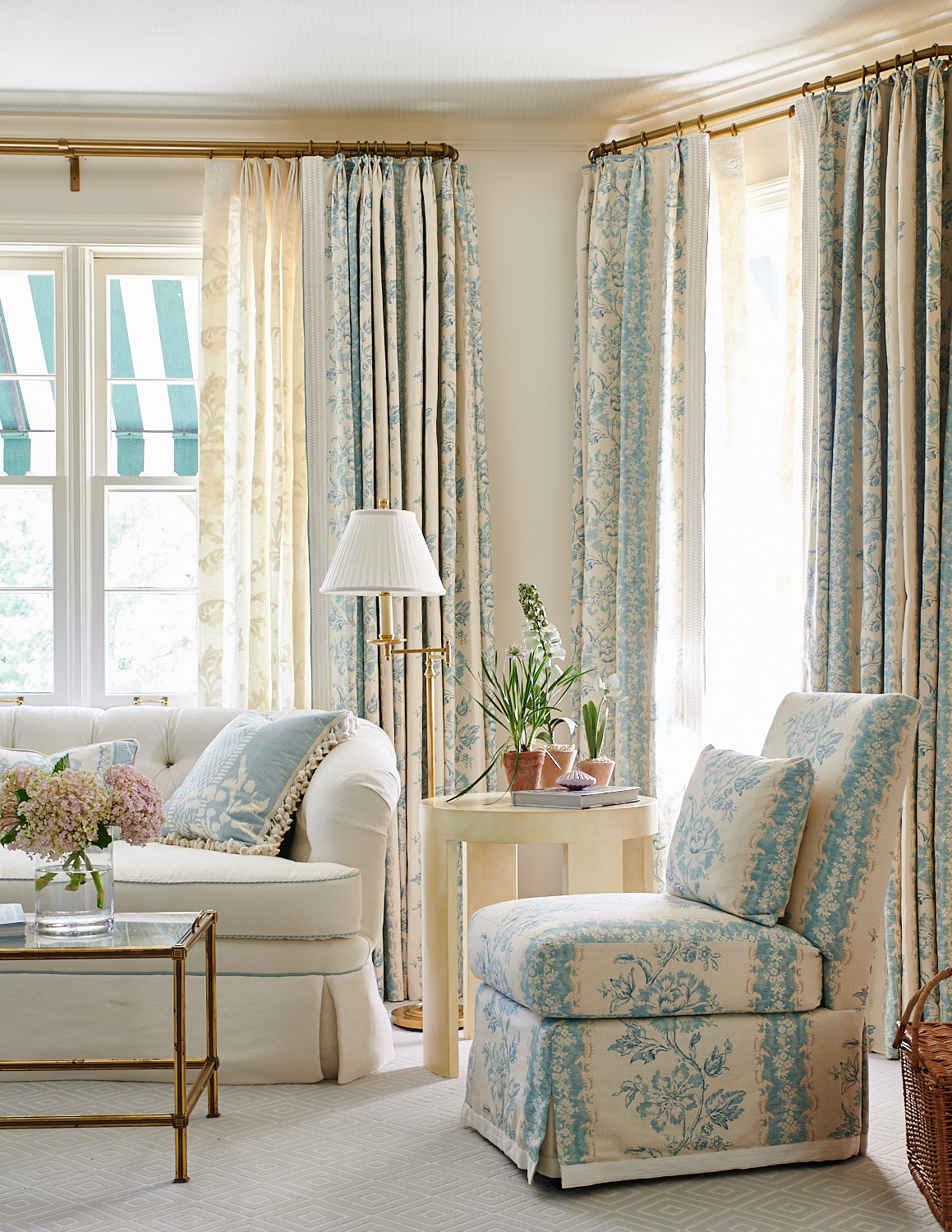 Window sheers and blackout drapes, back-tufted sofa with tasseled pillows