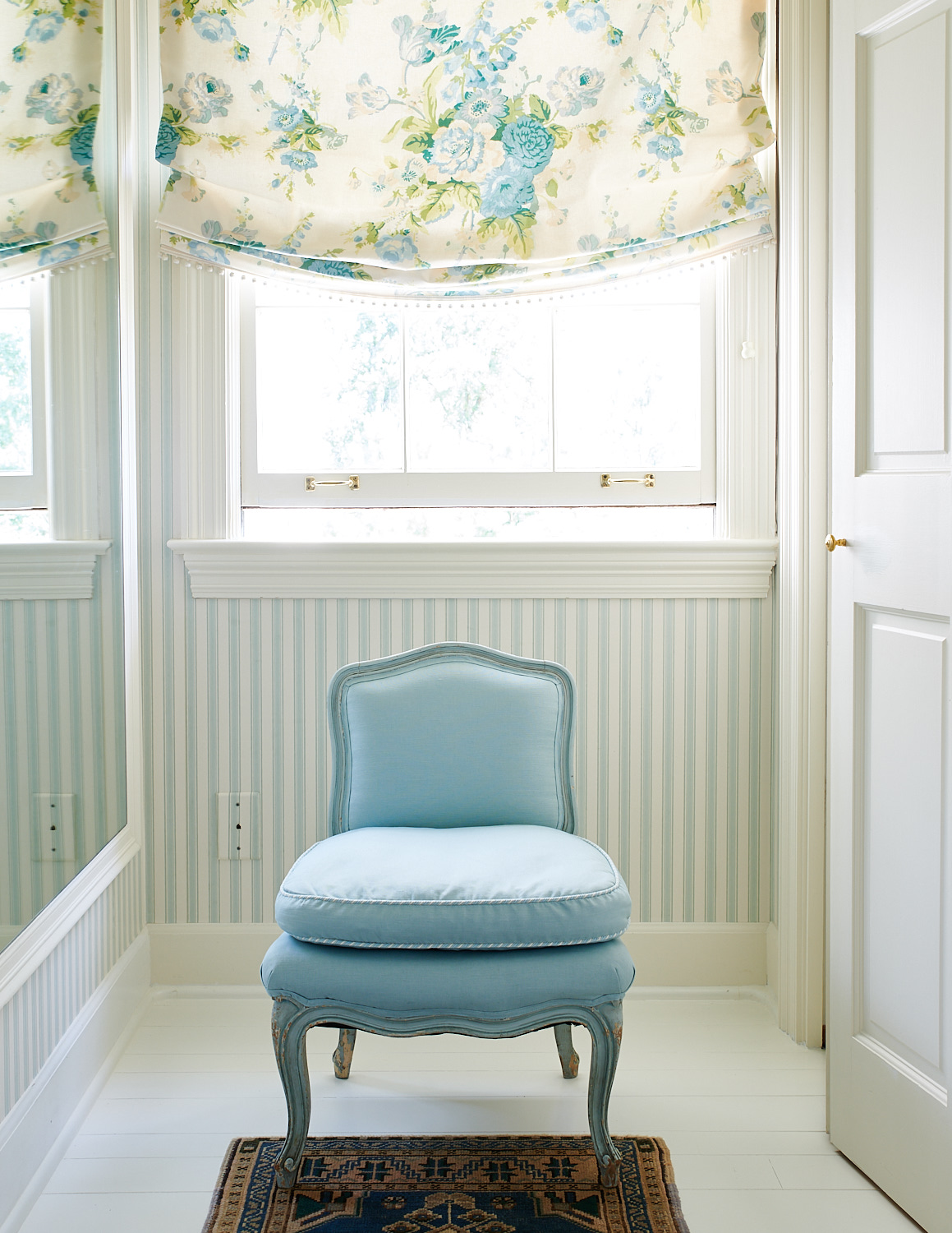 Floral roman shades with baby blue upholstered chair and matching trimmed cushion