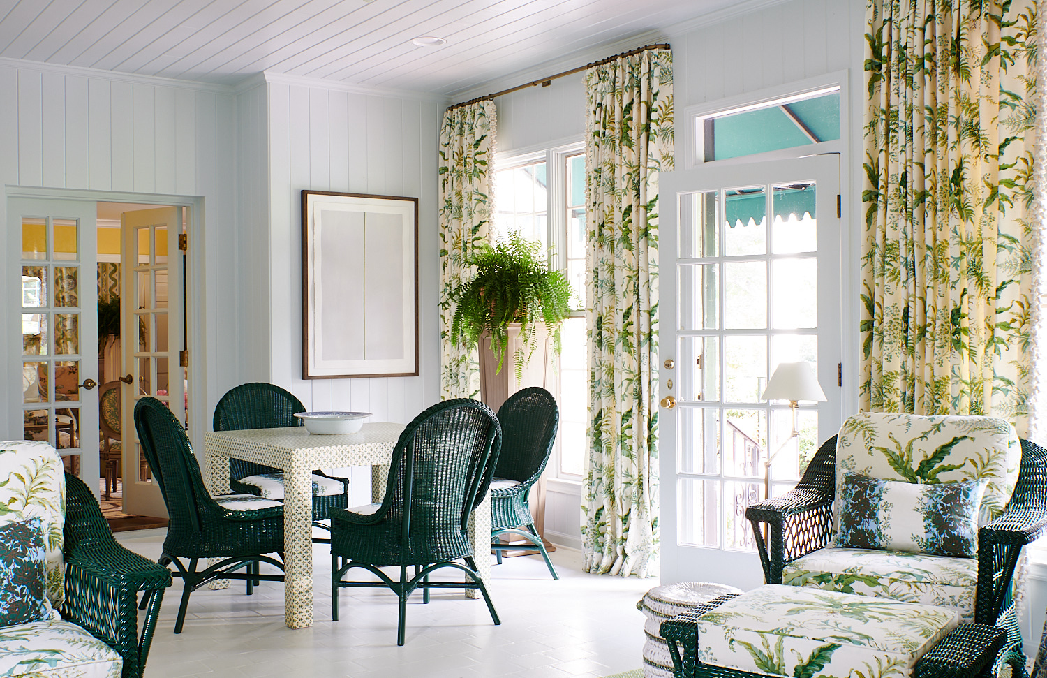 Wide view sun room with floral roman shades, wicker tea chairs with matching cushions and ottomans
