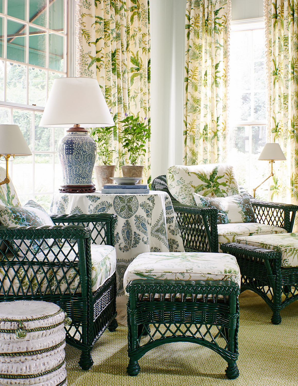 Floral drapery, wicker chairs and ottomans with matching floral cushions