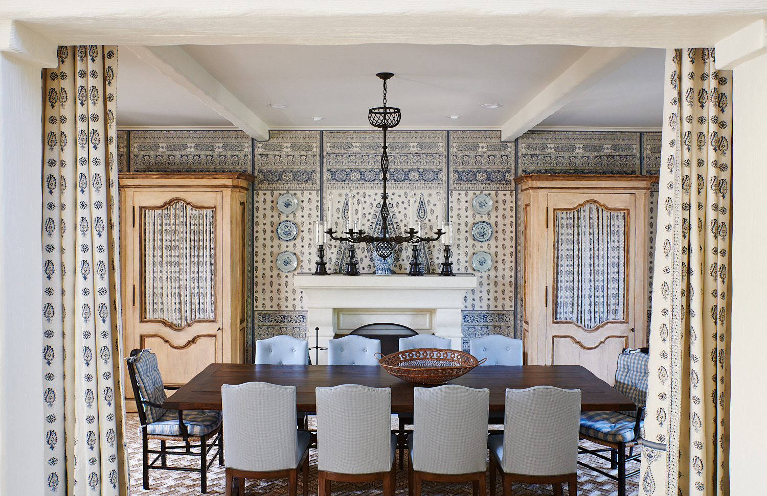 Armoire with paisley-patterned covers, tufted dining room chairs, and space-sectioning drapery