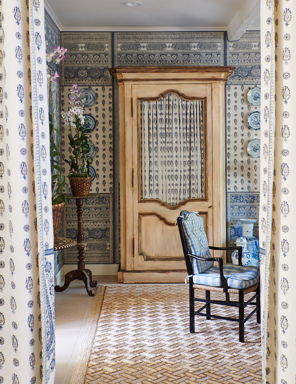 Armoire with paisley-patterned covers and plaid-cushioned seat