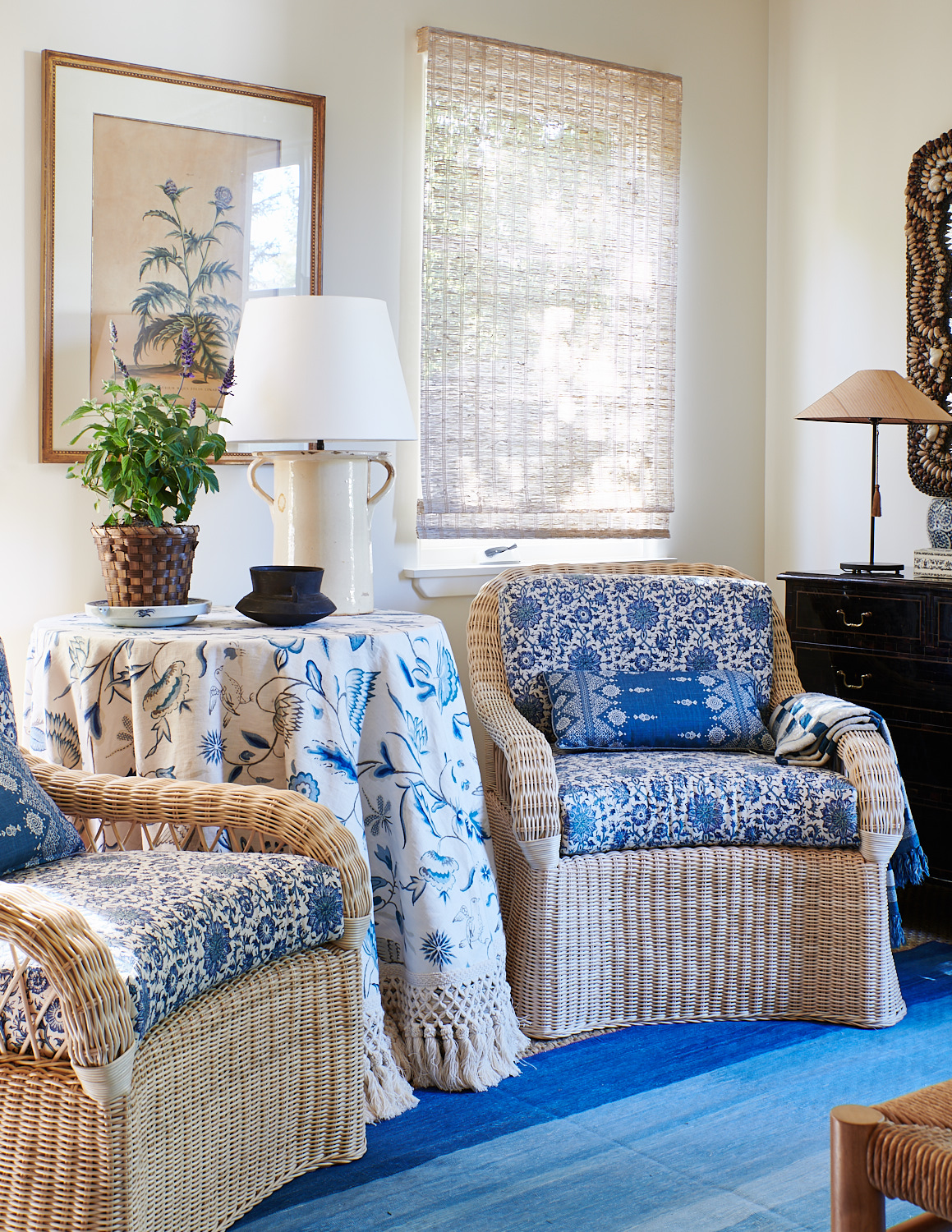Bamboo roman shades, wicker tea chairs with patterned cushions and kidney pillows