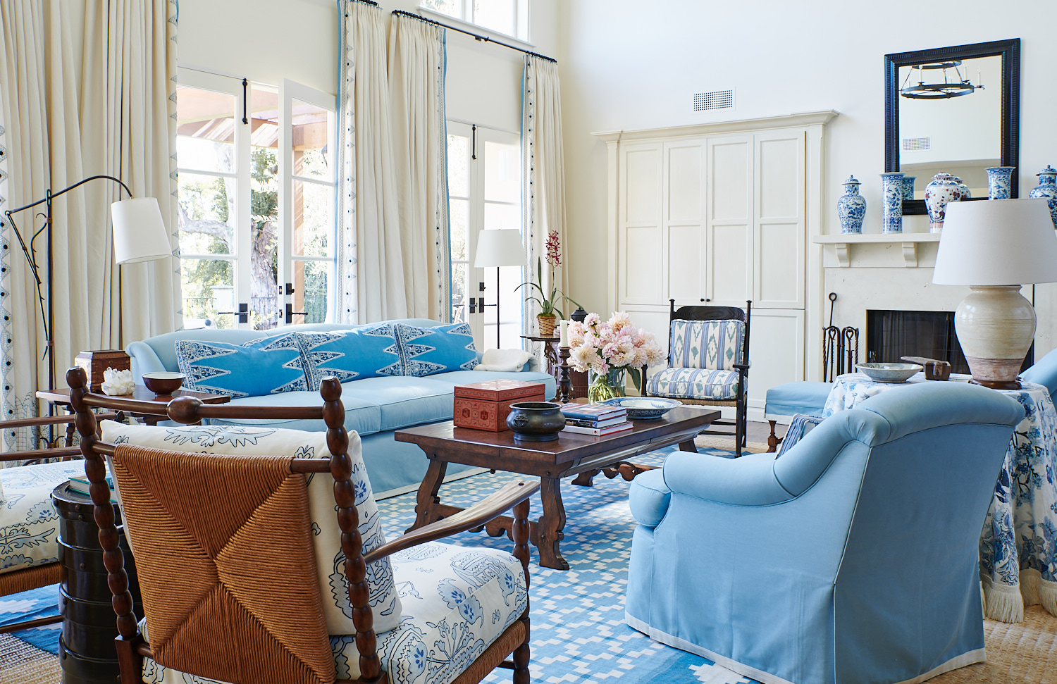 Wide view of upholstered chair, sofa with complementing back pillows, wicker chair cushions, and lofty drapery