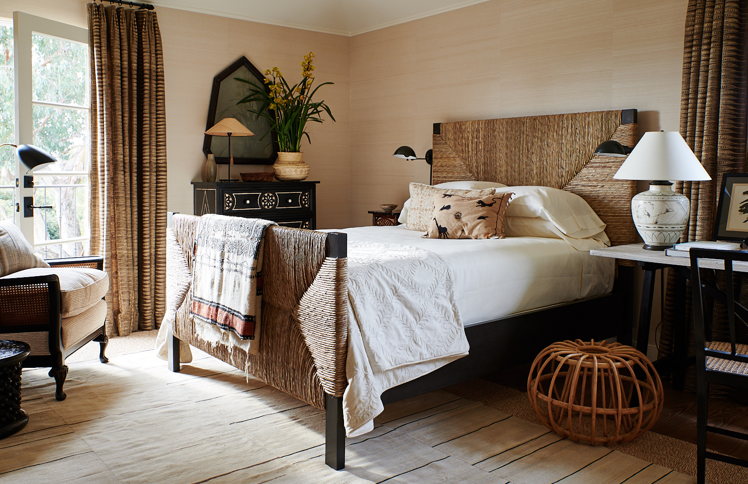 Wicker bed with custom pillows and tassels, upholstered wicker chair, and window drapes