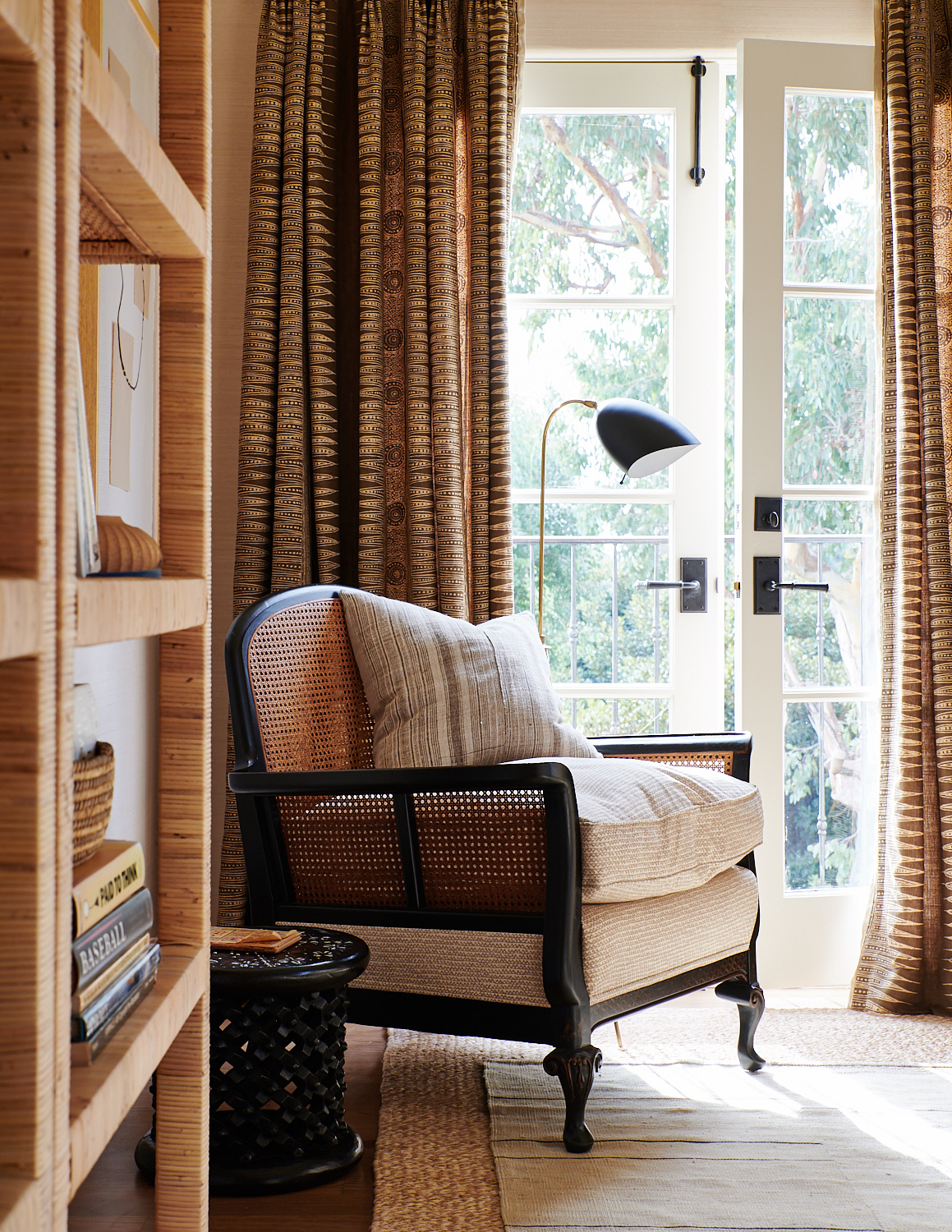 Upholstered wicker chair with added cushion and back pillows, and window drapes