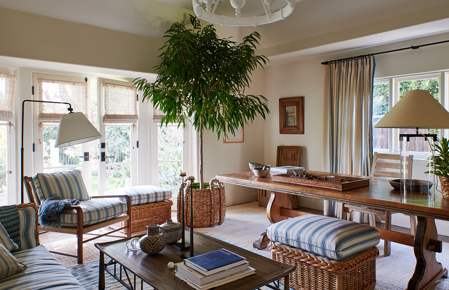 Wide view of office space with cane wicker chairs and striped cushions, bamboo roman shades, and pleated drapery