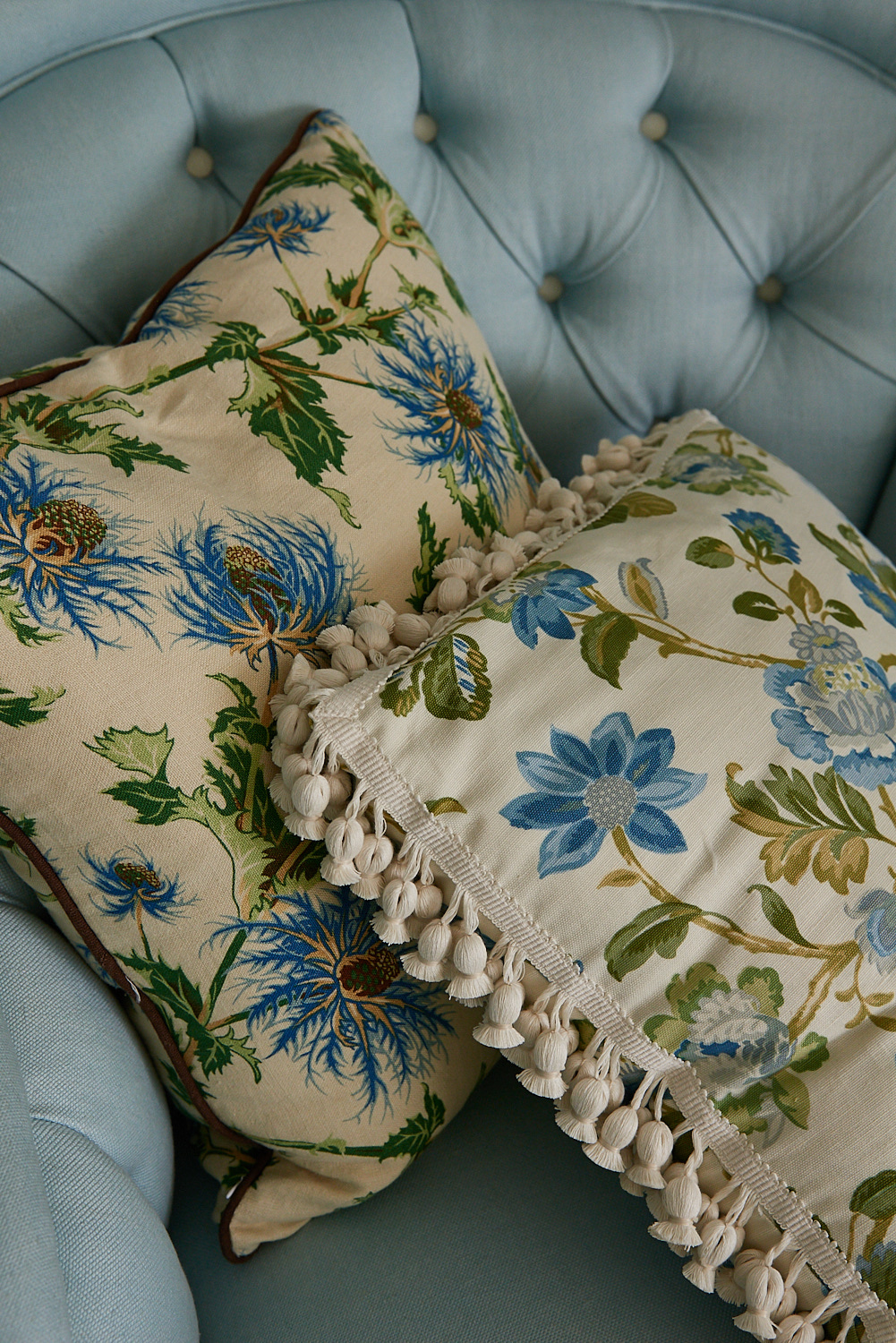 Grey tufted chair with floral custom pillows and tassels