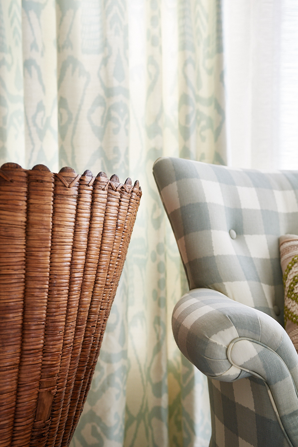 Upholstered plaid chair with tufts and background drapery
