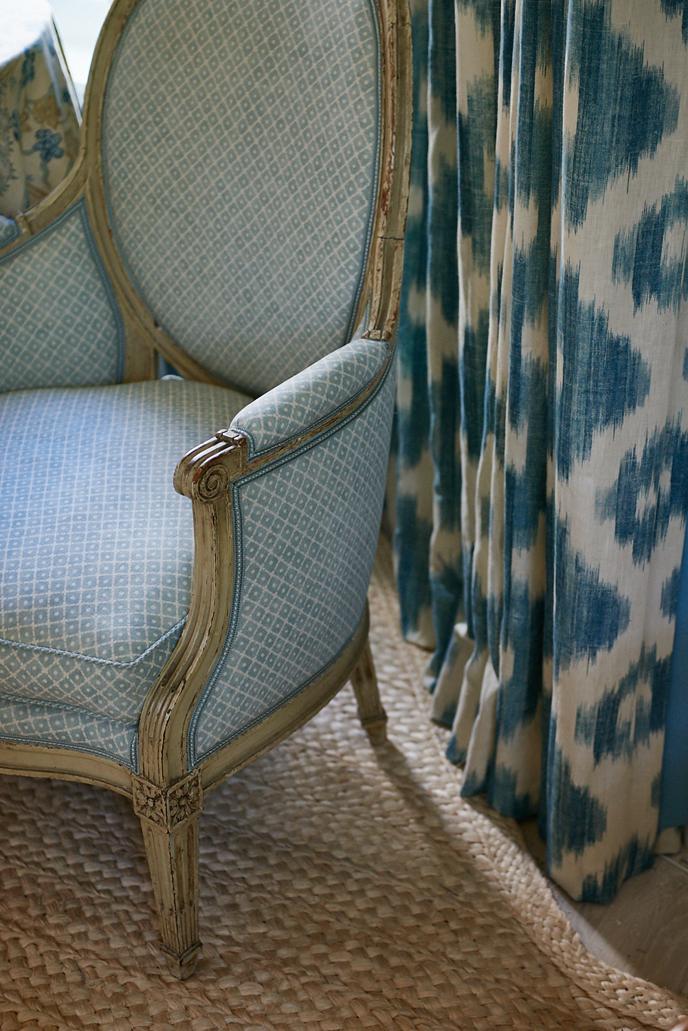 Detail of upholstered chairs and pleated blackout drapes