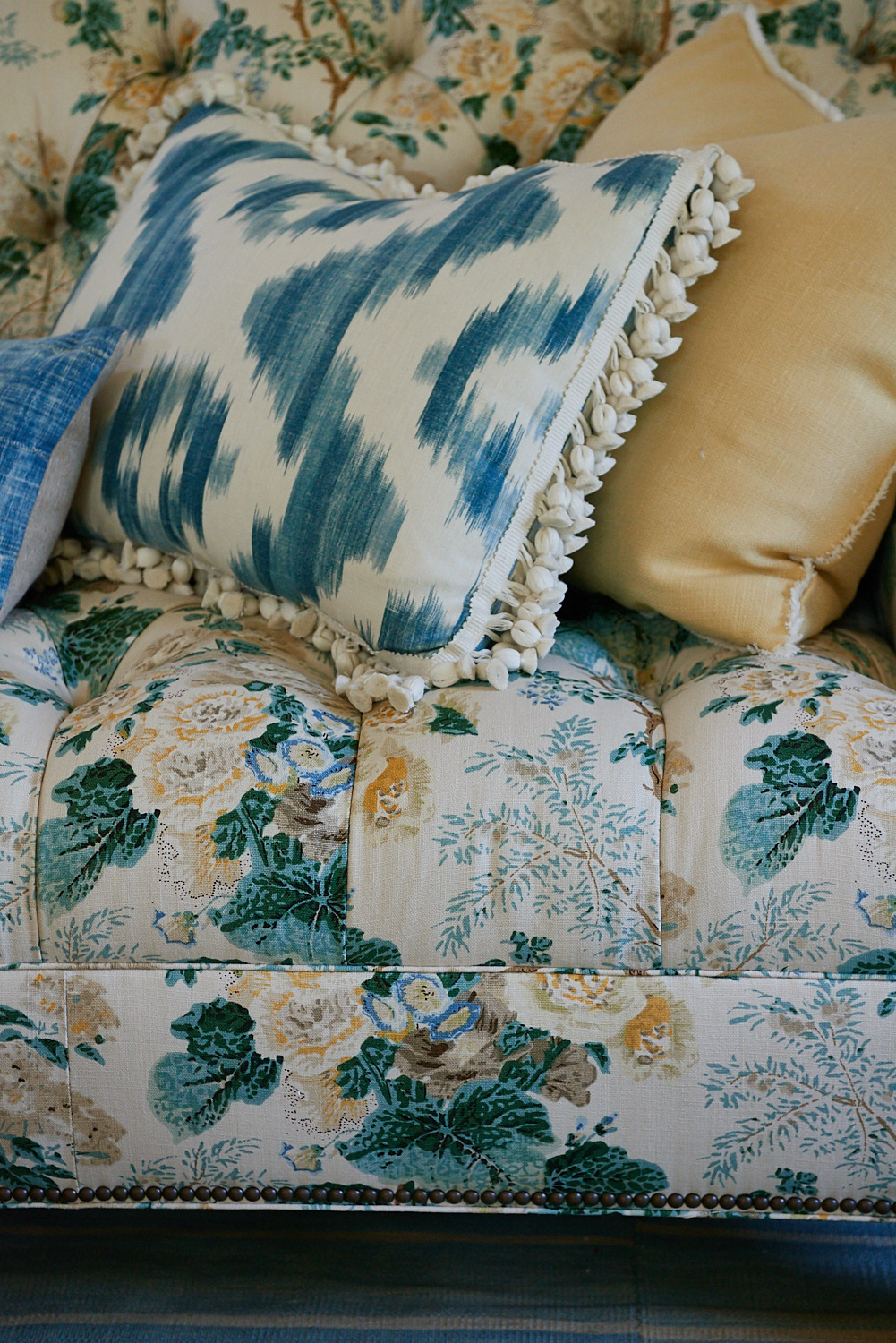 Detail of upholstered sofa with base rivets, and custom pillows with tassels