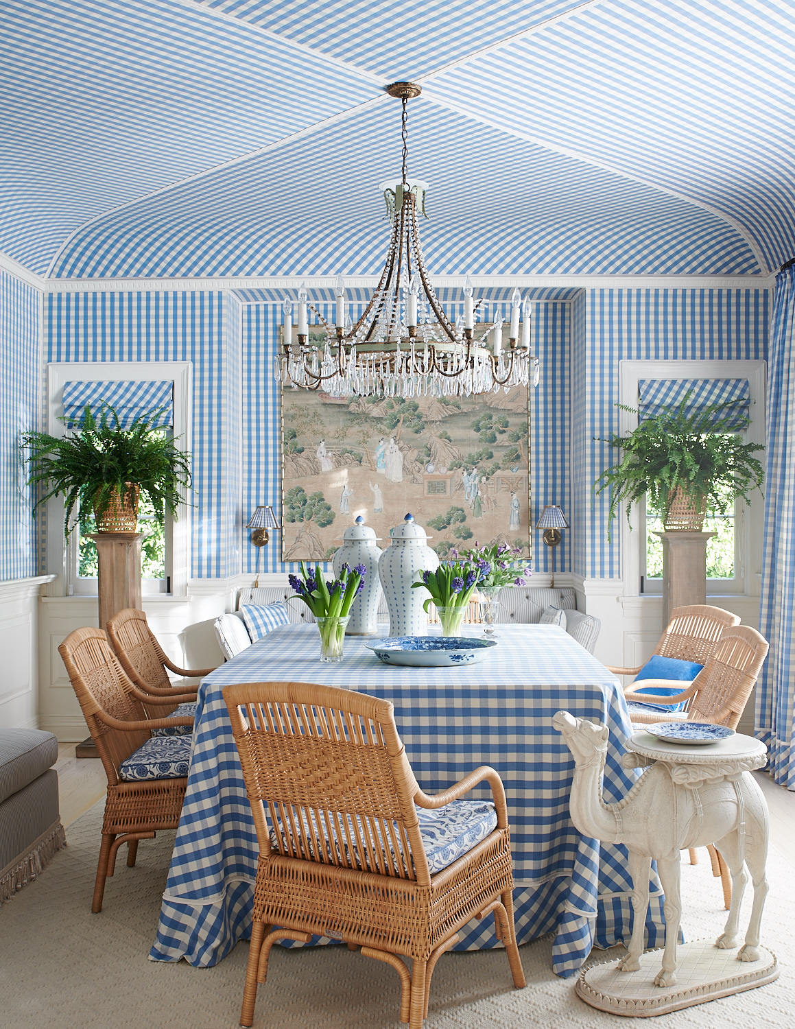 Custom checkered wall upholstery, roman shades, and custom seat pillows on cane chair