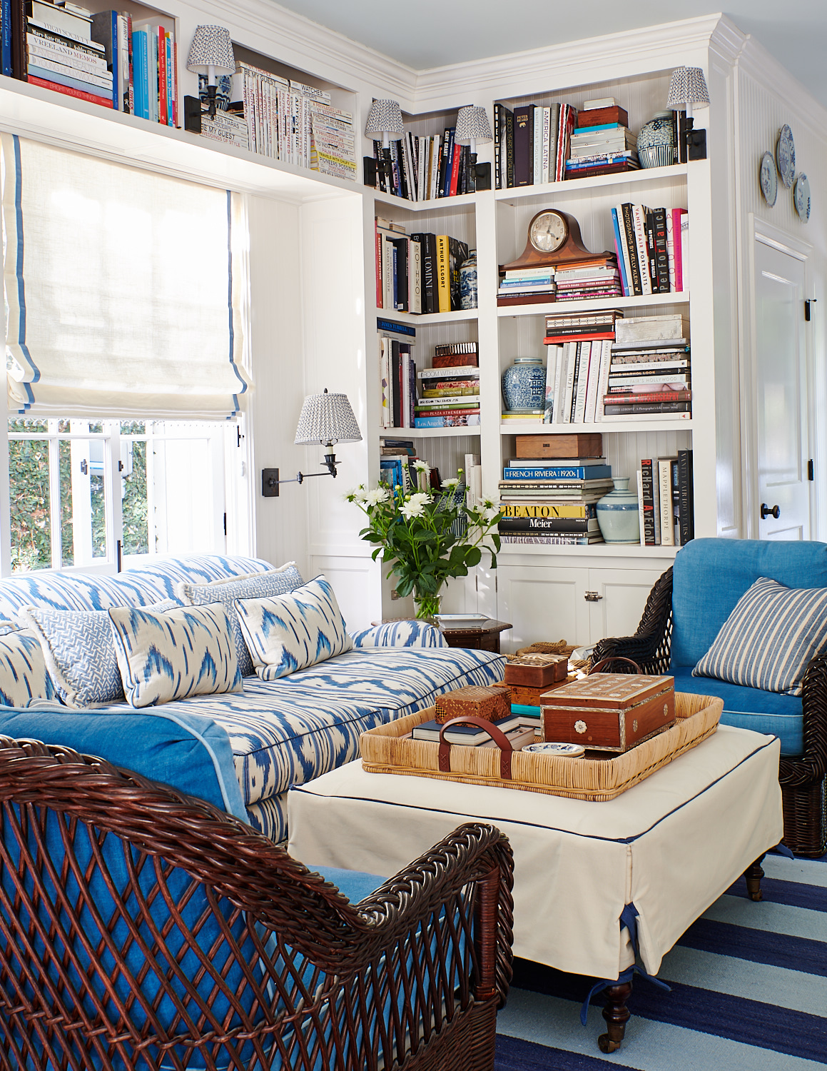 Roman shades, wicker club chairs with turquoise cushions, and cream ottoman with fitted slipcover