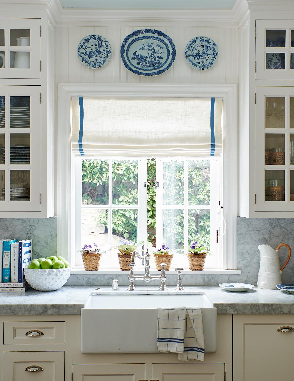 Roman shades bedeck the kitchen's French windows
