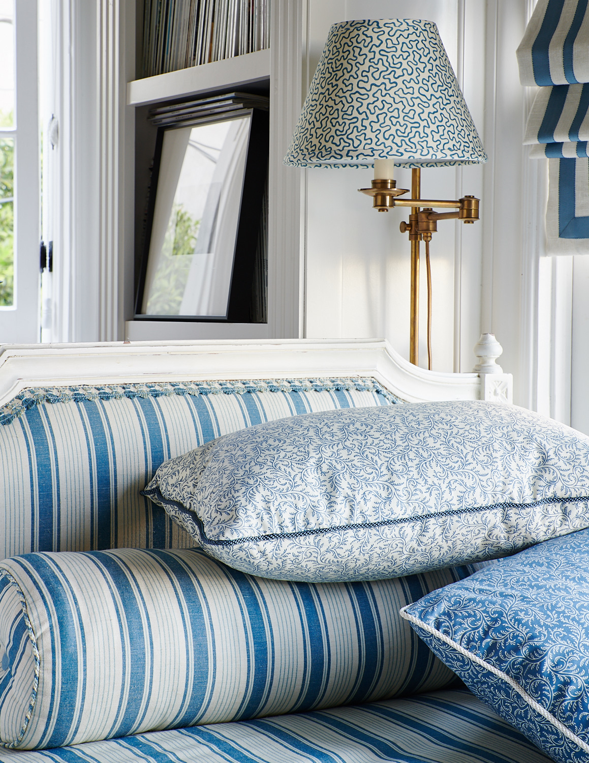 Detail of tasseled day bed with bolster pillows and matching pillows