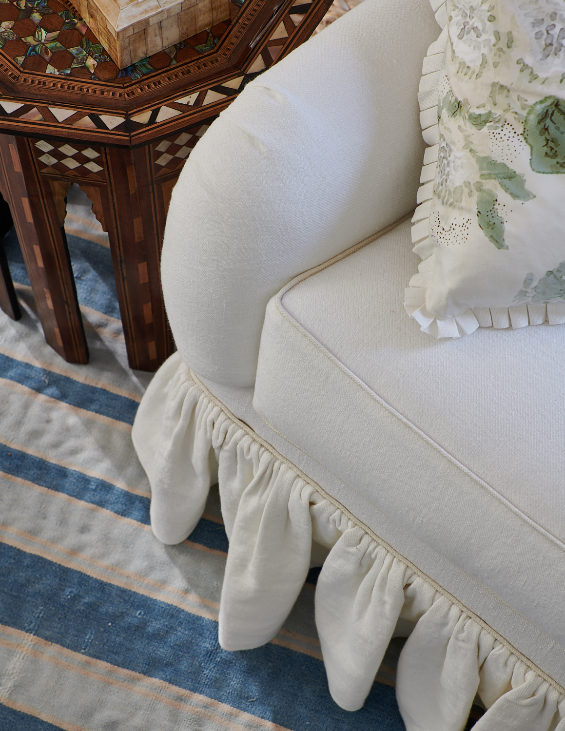 White trim upholstered chair with matching pleats and accompanying patterned pillow