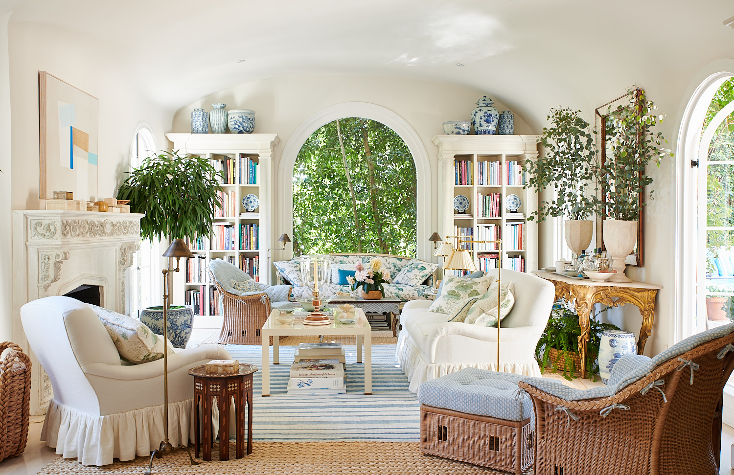 Living room view including diamond pattern cushions for cane chairs, upholstered bench with metal studs, and white sofa with pleats