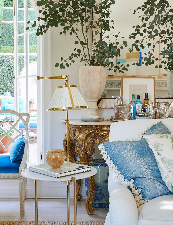 White sofa and tasseled throw pillows, with blue velvet upholstered sitting chair